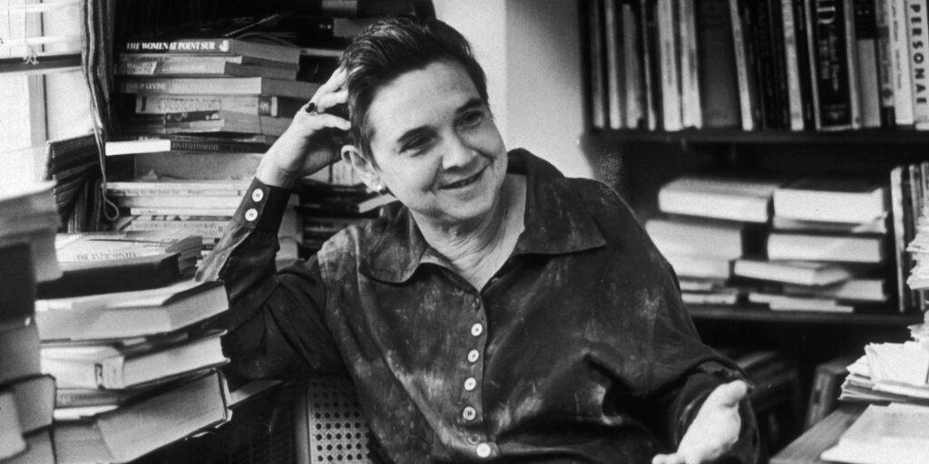 8th May 1987: American poet Adrienne Rich gestures and smiles while sitting in an office at W. W. Norton Publishers, 500 Fifth Avenue, New York City. (Photo by Neal Boenzi/New York Times Co./Getty Images)
